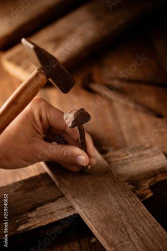 Fotografie, Obraz  man driving a nail on a wooden cross.