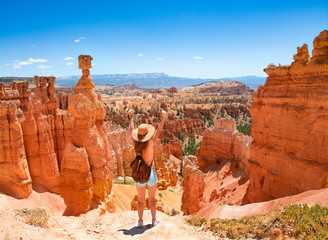 Girl with raised hands relaxing on top of the mountain, looking at beautiful mountain view.Young woman standing next to Thor's Hammer hoodoo with raised hands. Bryce Canyon National Park, Utah, USA
