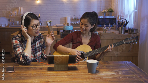 group of female best friends together indoor in apartment kitchen having fun and playing music with guitar. girl singing enjoy closed eyes wear glasses and headphones sitting at wooden table at night - 259553205