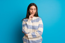 Young Woman Over Blue Wall Looking Down With The Hand On The Chin