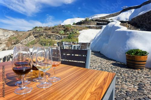 Fototapeta Glasses of wine in a terrace, Santorini, Greece. obraz