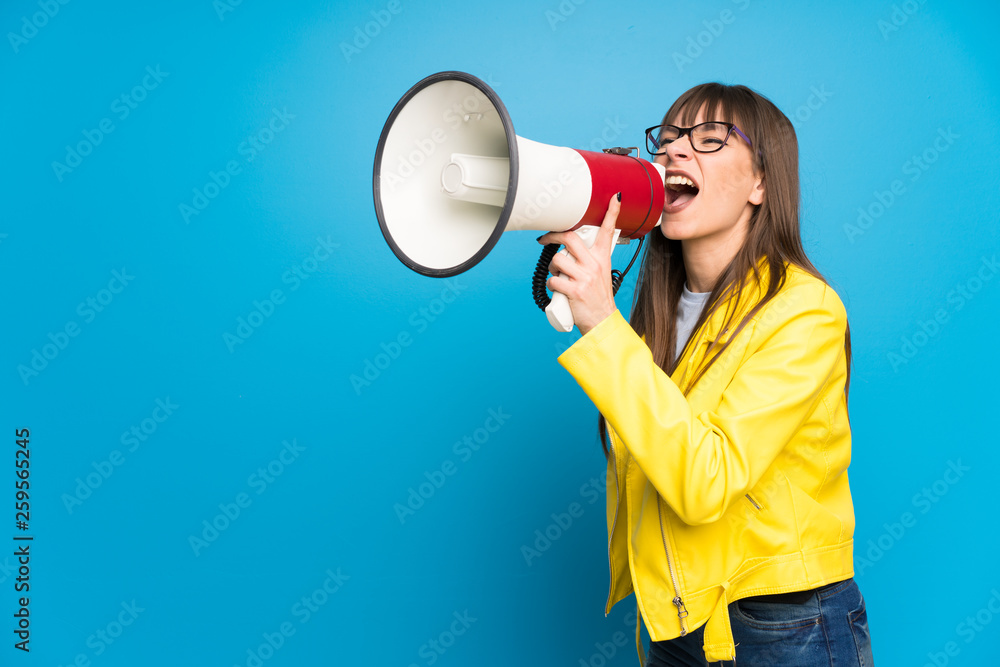 Fototapeta Young woman with yellow jacket on blue background shouting through a megaphone