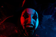 Creepy Screaming Jester's Face With Black Eyes And Fangs, Close-up.