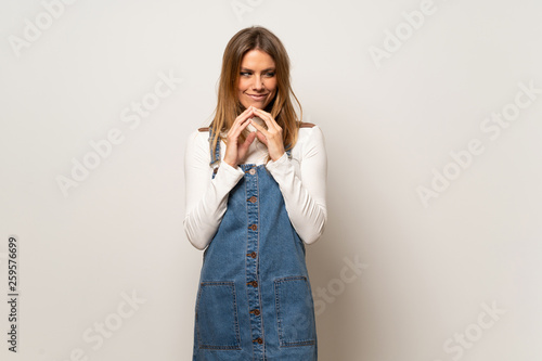 Fotografie, Obraz  Beautiful woman over isolated white wall scheming something