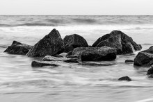 Slow Shutter Speed Of The Tide Coming In Over Rocks On The Beach.