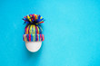 white egg in knitted wool colored hat on blue background, easter concept, copy space