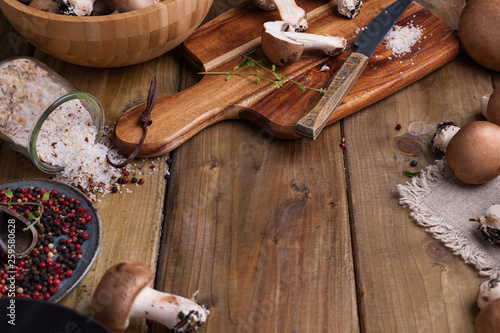 Poster Cuisine Champignon mushrooms with red onions and spices on a wooden background, wooden utensils. Rustic style photo. Vegetarian lunch of vegetables. Place for text