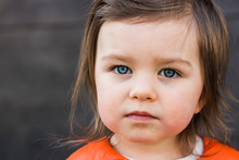 Child Toddler Portrait Closeup. Beautiful Baby Girl With Blue Eyes Looks Seriously