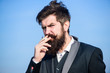 Taking a break to smoke. Bearded man smoking cigarette. smoke. brutal caucasian hipster with moustache. Future success. Male formal fashion. Businessman against the sky. Mature hipster with beard