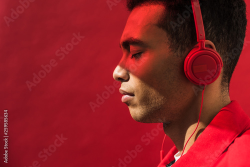 Fotografía  side view of handsome mixed race man in headphones with eyes closed isolated on
