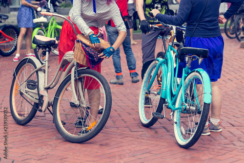 Foto op Plexiglas Fiets Concept: women on bicycles. Woman in bright clothes hold the handlebars.