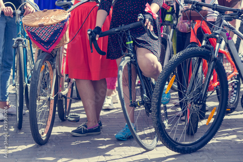 Concept: women on bicycles. Woman in bright clothes hold the handlebars.