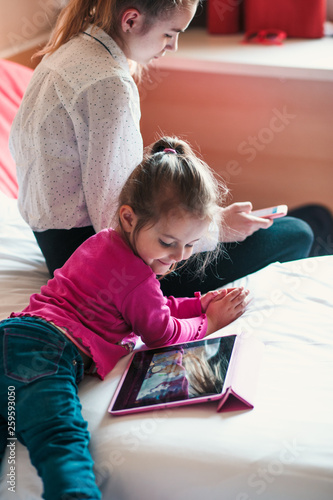 Teenage girl using mobile phone together with her little sister watching animate Canvas-taulu