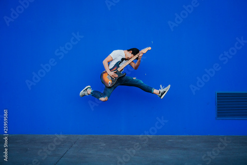 Valokuva  young man jumping with electric guitar on blue background