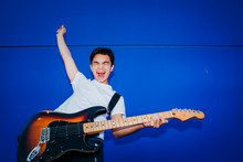 Young Man With Electric Guitar On Blue Background