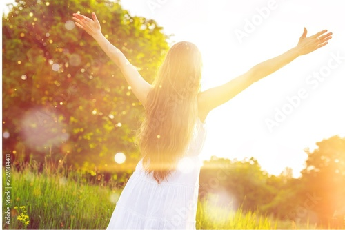 Young woman on field under sunset light Canvas-taulu