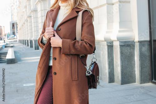 Fototapeta Stylish fashionable blonde woman wearing coat and sunglasses, street style photo