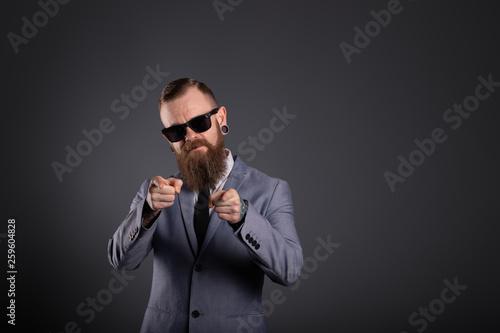 Fotomural  Geschäftsmann mit Bart telefoniert mit Handy zeigt Finger Sonnenbrille
