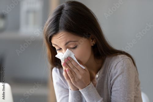 Sick young woman holding tissue and blowing her running nose Canvas Print