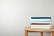 canvas print picture - Stack of books on table against light background. Space for text