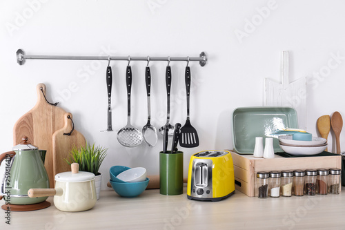 Cuadros en Lienzo  Set of clean cookware, dishes, utensils and appliances on table at white wall