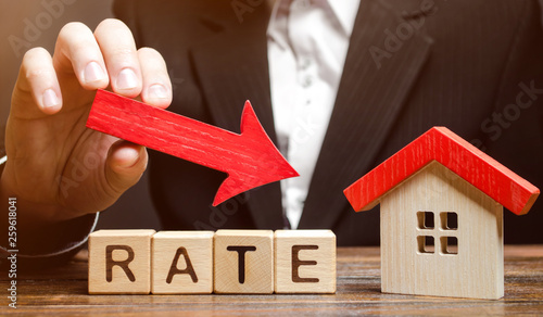 Fotografia Businessman holding the down arrow on wooden blocks with the word Rate and house