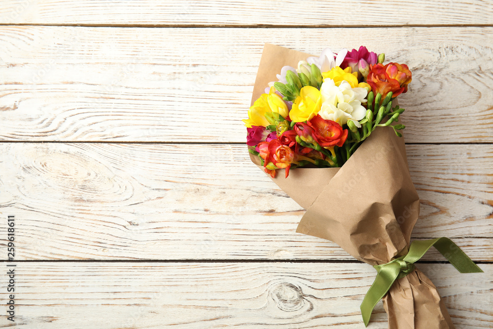 Fototapety, obrazy: Bouquet of beautiful spring freesia flowers on wooden background, top view. Space for text