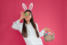 Beautiful Woman In Bunny Ears Headband With Basket Of Easter Eggs On Color Background