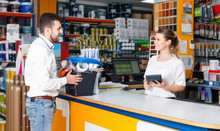 Woman Seller Consulting   Male Customer At The Counter  In Tool-ware Shop