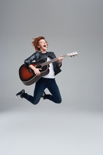 Young Woman Musician With An Acoustic Guitar In Hand On A Gray Background. She Laughs And Jumps High. Plays Rock And Roll Loudly. Full-length Portrait.