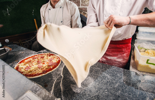 Foto op Canvas Pizzeria Preparation of a pizza dough, a dough in flight.