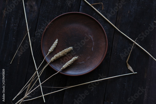 Valokuva  three wheat spikelets on a clay plate on a black burnt wooden background