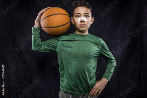 Photo Confident young athlete holding a basketball.