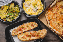 Take Away Italian Pasta Food. Pizza With Box Green Peppers, Garlic Bread, Fetuccine And Ravioli On Plastic Box.