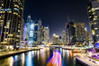 Stunning view of the Dubai Marina at dusk with illuminated skyscrapers in the background and a light trails left by a yacht sailing in the foreground. Dubai, United Arab, Emirates.