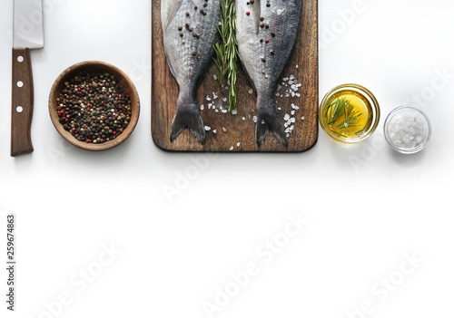 Fototapeta  Board with fresh dorado fish, knife and spices on white background