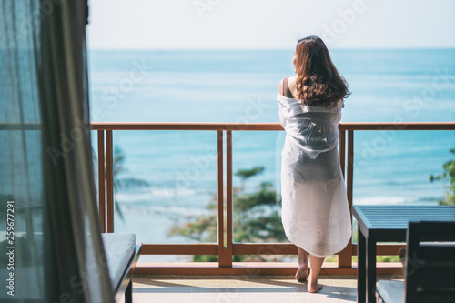 Fototapeta A beautiful asian woman standing and enjoy watching the sea view at balcony
