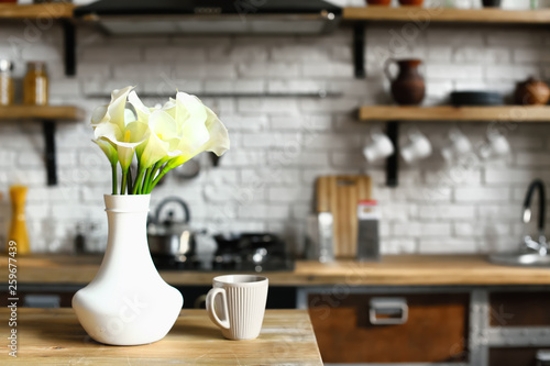 Fotografie, Obraz  Vase with beautiful flowers and cup of coffee on table in kitchen