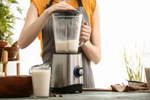 Woman Making Hazelnut Milk In Kitchen