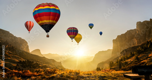 Fotobehang Ballon Beautiful panoramic nature landscape of countryside mountains with colorful high hot air balloons festival in summer sky. Vacation travel panorama background.