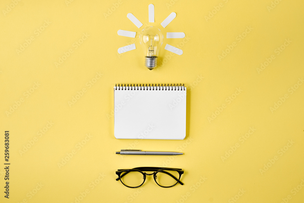Fototapety, obrazy: Financial planning table top with pen, notepad, eyeglasses and light bulb on yellow background. Concept brainstorming and new idea