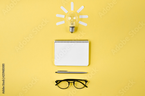 Obraz Financial planning table top with pen, notepad, eyeglasses and light bulb on yellow background. Concept brainstorming and new idea - fototapety do salonu
