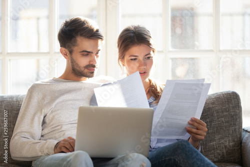 Fotografie, Obraz  Focused couple sitting on couch reading received formal letter