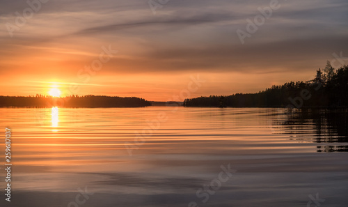 Spoed Fotobehang Oranje eclat Scenic sunset landscape with water reflections and light waves at summer evening in Finland.