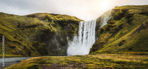 Photo Stands Waterfalls Beautiful scenery of the majestic Skogafoss Waterfall in countryside of Iceland in summer. Skogafoss waterfall is the top famous natural landmark and tourist destination place of Iceland and Europe.