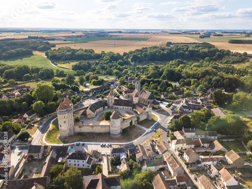 фотография  Medieval castle with fortified walls, towers and donjon in rural village in Fran