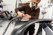 Professioneller Autolackierer schleift ein Autoteil mit der Schleifmaschine vor in einer Werkstatt - Serie Autowerkstatt