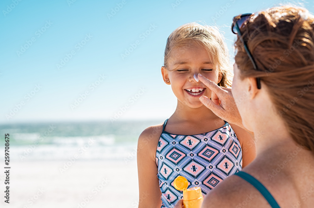 Fototapety, obrazy: Mother applying suntan lotion on daughter face