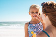 canvas print picture - Mother applying suntan lotion on daughter face