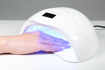 Closeup view of female hands with fresh beautiful pink modern gel polish manicure. Woman puts hand into led uv lamp for curing top cover of nailpolish. Horizontal color photography.